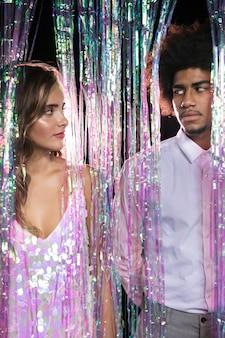 Homem e mulher se olhando de uma cortina de brilhos