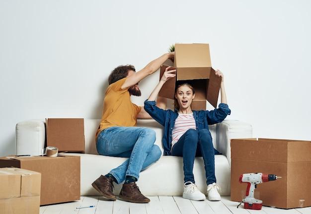 Homem e mulher se sentam em caixas de sofá brancas com coisas de estilo de vida em movimento.