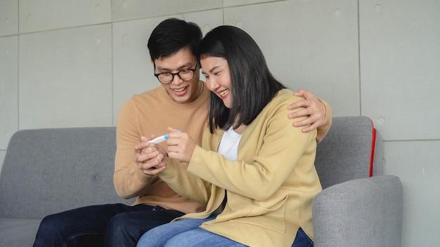Homem e mulher se sentindo empolgados depois de assistir a um teste de kit de gravidez na sala de estar