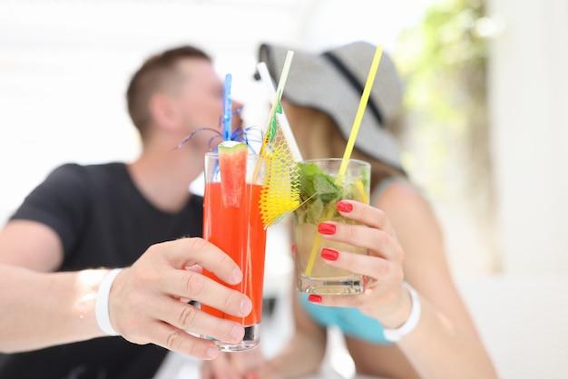 Homem e mulher segurando coquetéis alcoólicos e se beijando