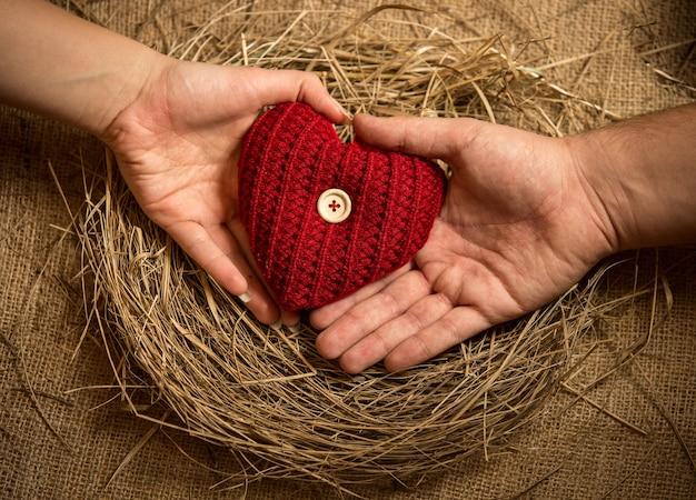 Homem e mulher segurando coração de malha em ninho de pássaros