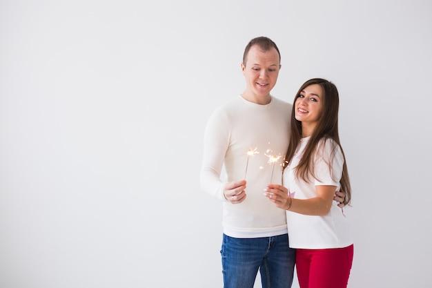 Homem e mulher segurando estrelinhas na parede branca