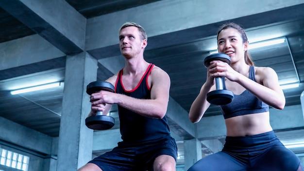 Homem e mulher segurando halteres exercem-se no ginásio de fitness
