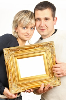 Homem e mulher segurando moldura de ouro velho