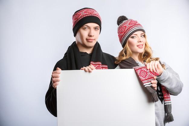 Homem e mulher segurando o cartaz branco