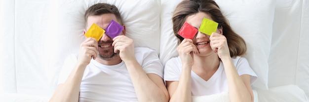 Homem e mulher segurando preservativos coloridos enquanto estão deitados na cama, conceito de vida íntima segura