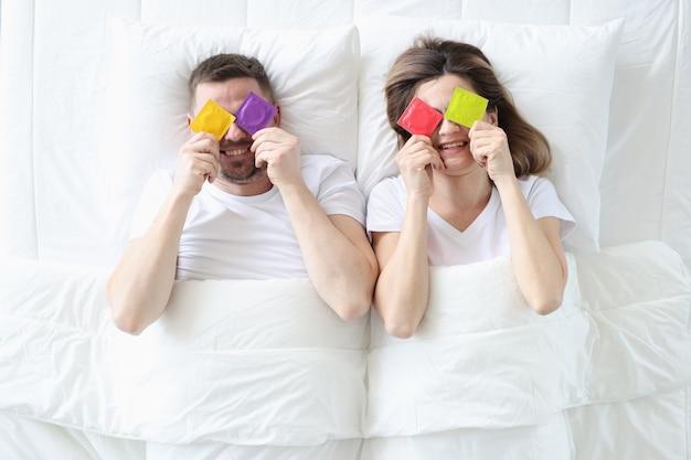 Homem e mulher segurando preservativos coloridos