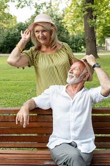 Homem e mulher segurando seus chapéus