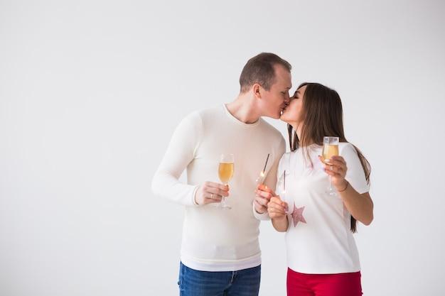 Homem e mulher segurando taças de champanhe e estrelinhas enquanto se beijam