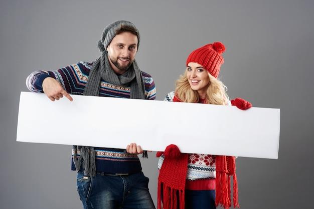 Homem e mulher segurando um cartaz branco vazio