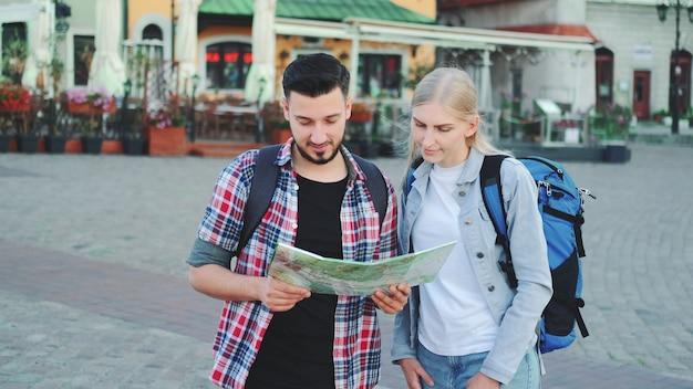 Homem e mulher segurando um mapa e procurando algum lugar na praça da cidade