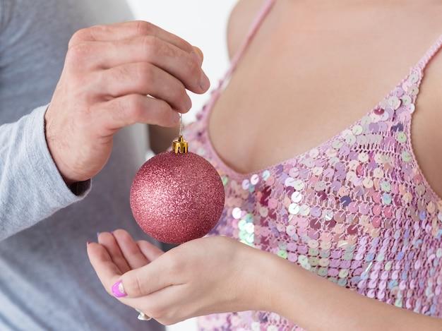 Homem e mulher segurando uma bola brilhante de ouro rosa nas mãos. conceito de ornamento festivo do feriado.