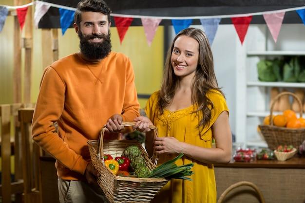 Homem e mulher segurando uma cesta de legumes na mercearia