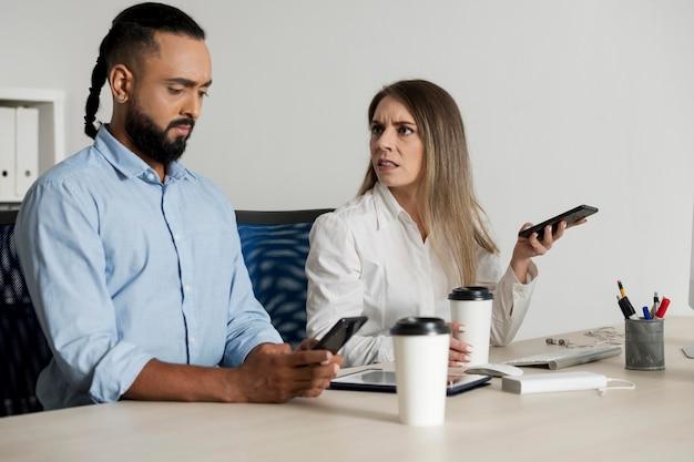 Homem e mulher sendo viciados em seus telefones, mesmo no trabalho