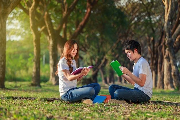Homem e mulher sentada e lendo um livro no parque