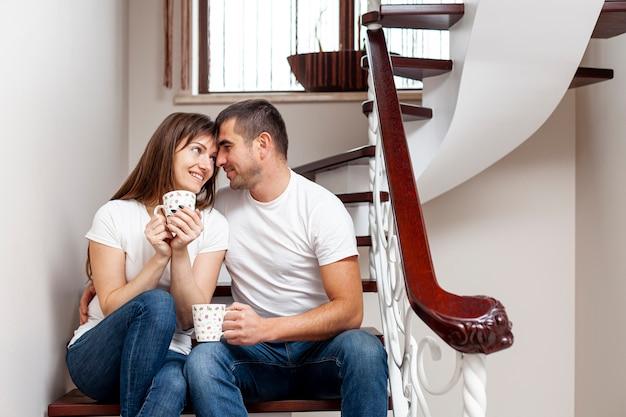 Homem e mulher sentada na escada e tomando café