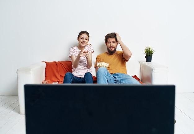 Homem e mulher sentada no sofá, assistindo a um filme de entretenimento de pipoca. foto de alta qualidade