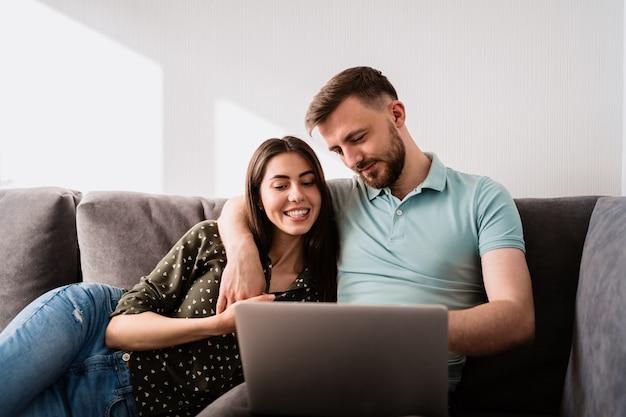Homem e mulher sentada no sofá com um laptop