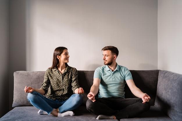 Homem e mulher sentada no sofá em pose de lótus