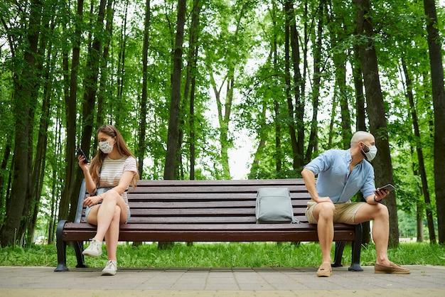 Homem e mulher sentados em extremos opostos do banco, mantendo distância um do outro para evitar a propagação do coronavírus.