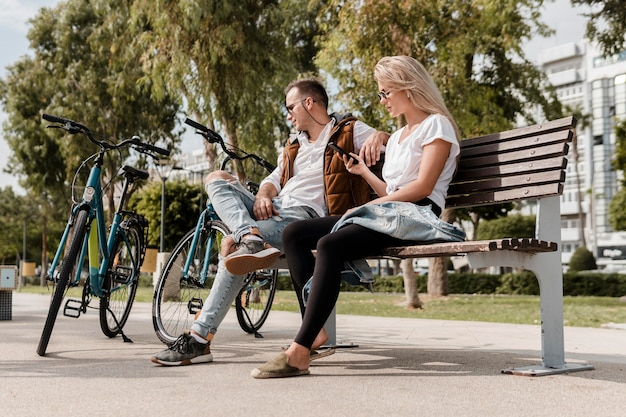 Homem e mulher sentados em um banco ao lado de suas bicicletas