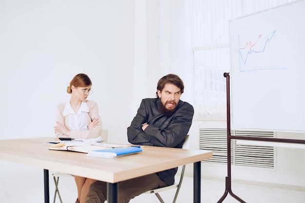 Homem e mulher sentados na mesa de comunicação emoções trabalho colegas insatisfação. foto de alta qualidade
