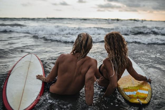 Homem e mulher sentados na praia com pranchas de surf