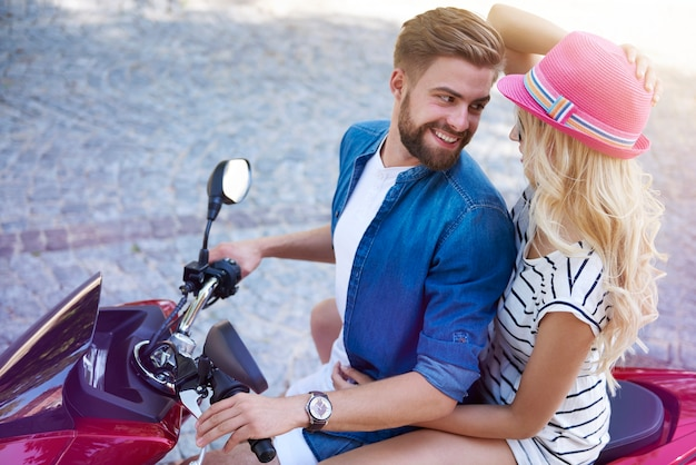 Homem e mulher sentados na scooter
