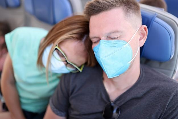 Homem e mulher sentados no assento usam máscara protetora e dormem