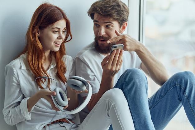 Homem e mulher sentados no parapeito da janela juntos tecnologia de apartamentos