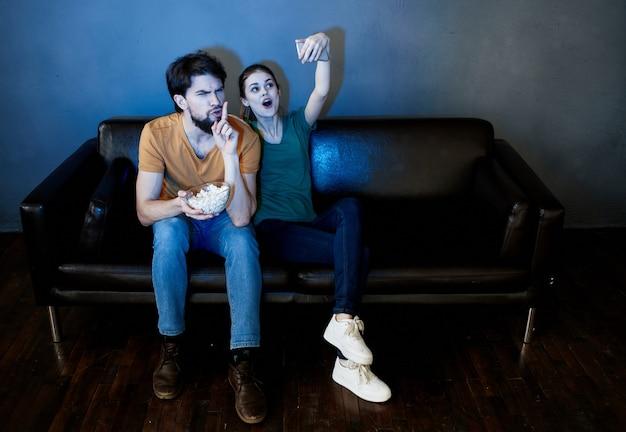 Homem e mulher sentados no sofá em frente à tv dentro de casa