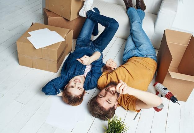 Homem e mulher sentados no sofá em um apartamento novo