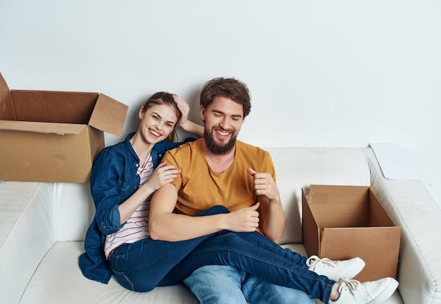 Homem e mulher sentados no sofá movendo caixas com coisas para inauguração de casa em família