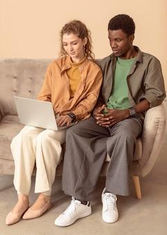 Homem e mulher sentados no sofá usando o laptop
