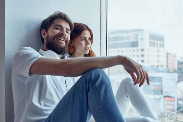 Homem e mulher sentados perto da janela com fones de ouvido, alegria romântica