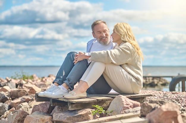 Homem e mulher sentados perto do mar conversando