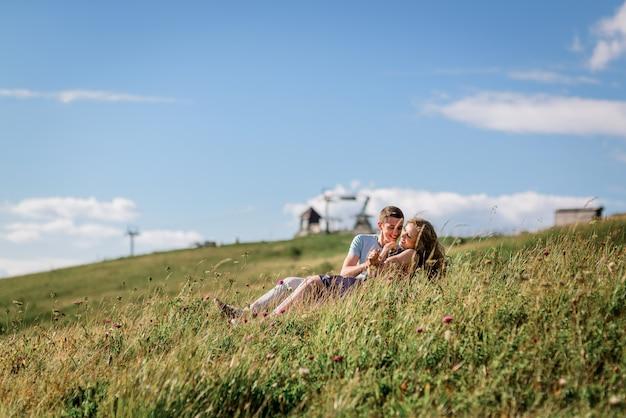 Homem e mulher sentam-se abraçando na grama antes da linda paisagem