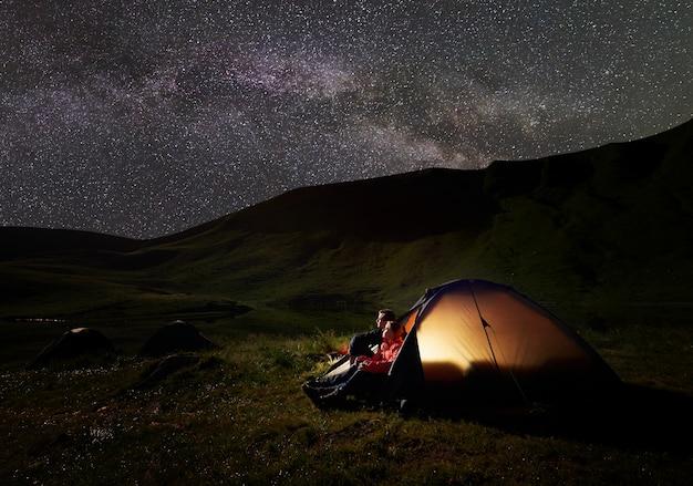Homem e mulher sentam-se em uma tenda, olhando o céu repleto de estrelas, montanhas poderosas e um lago ao pé. na tenda, as luzes acendem. o conceito de recreação ativa nas montanhas