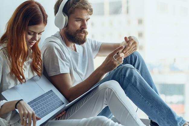 Homem e mulher sentam-se perto da janela com fones de ouvido e adoram tecnologia de estilo de vida. foto de alta qualidade
