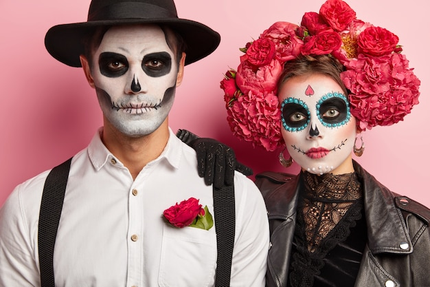Homem e mulher sérios têm imagem tradicional mexicana, usam caveiras de açúcar, vestidas com traje especial para festa à fantasia, ficam de perto, isolado sobre fundo rosa.