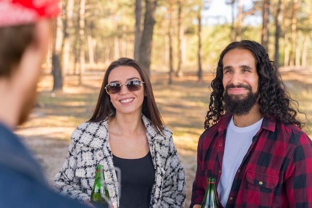 Homem e mulher sorridente conversando com um amigo ao ar livre Foto gratuita