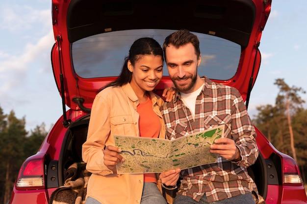 Homem e mulher sorridente de vista frontal verificando um mapa