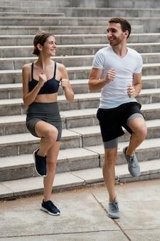 Homem e mulher sorridente fazendo exercícios nos degraus