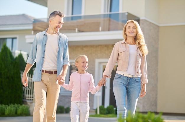 Homem e mulher sorrindo caminhando com a filha pela rua