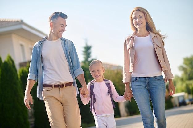 Homem e mulher sorrindo caminhando com a filha