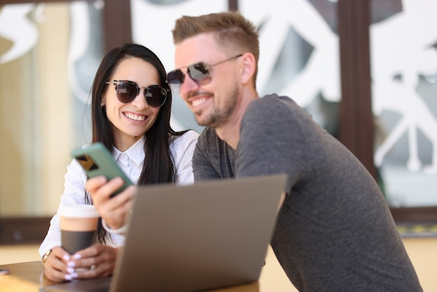 Homem e mulher sorrindo com óculos de sol se comunicam no café perto do laptop