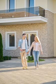 Homem e mulher sorrindo e andando de mãos dadas