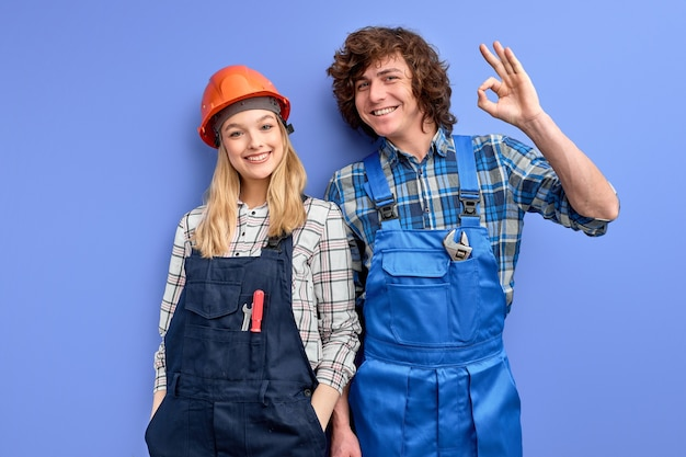 Homem e mulher sorrindo, engenheiros civis, vestindo uniforme e capacete, trabalhando na fábrica industrial.
