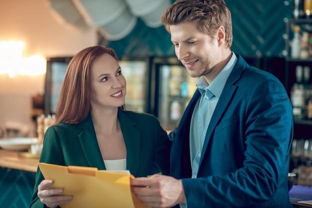 Homem e mulher sorrindo, olhando documentos