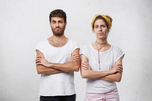 Homem e mulher teimosos e raivosos, em posturas fechadas, mantendo os braços cruzados, enfrentando desentendimentos em relacionamentos enquanto têm conflito ou briga